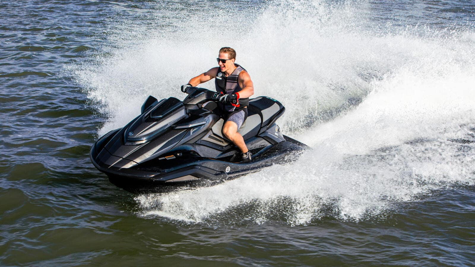 Our Packages: Image of a person riding a jet ski through waves.